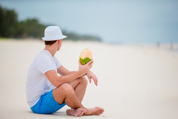Young man enjoy beach vacation and drinking coconut