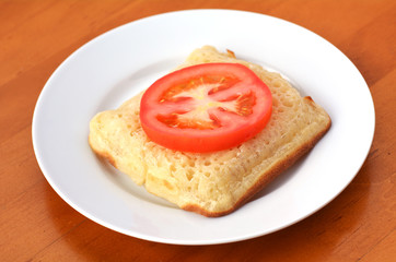 Square shape buttered English crumpet with slice of tomato