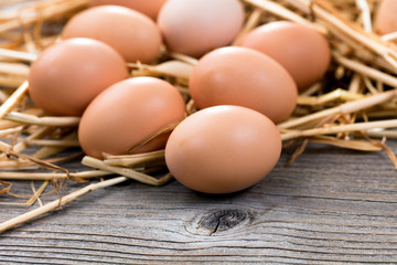 Fresh organic eggs on rustic wooden boards and straw
