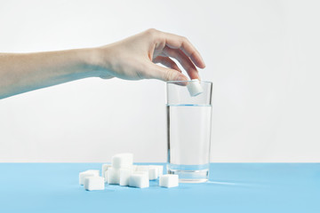 Glass of water against sugar, diabetes disease, sweet addiction, hand drop a sugar
