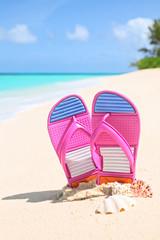 Pinks flip-flops on a sunny sandy beach..Tropical beach vacation