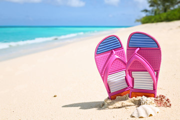 Pinks flip-flops on a sunny sandy beach..Tropical beach vacation