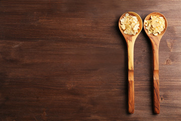 Two wooden spoons with almond flakes on the table, close-up