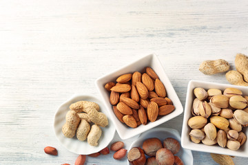 Pistachios, almonds, hazelnuts, peanuts and walnut kernels in the ceramic bowls, on white wooden backgrounds