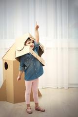 Little cute girl in astronaut helmet playing with cardboard space rocket in room