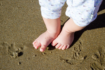 Baby feet on beach with sand