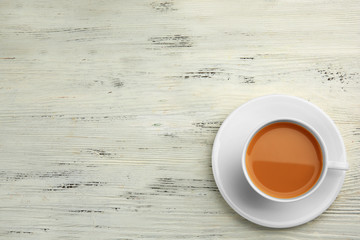 Porcelain cup of tea with milk on white wooden background