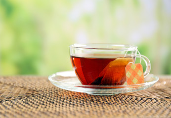 Black tea with bag in glass cup on green blurred background, close up
