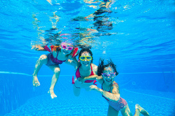 girls with mother playing  underwater