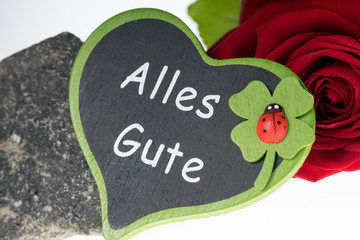 All the best / red rose and a stone with heart sign and the german words all the best