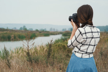 pretty playful country lady posing with camera against pond