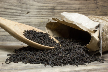 Dry tea leaves for black tea and wooden spoon on wooden background