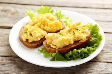 Scrambled eggs with bread and vegetables on a grey wooden table