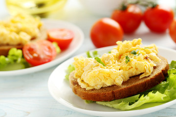 Scrambled eggs with bread and vegetables on a blue wooden table