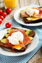 Poached eggs with avocado and bacon on toasts on grey wooden tab