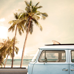 Wall Mural - Vintage car parked on the tropical beach (seaside) with a surfboard on the roof