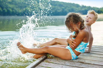Kinder plantschen mit Füßen im Wasser