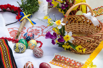 Easter holiday. Easter eggs with flowers on the Ukrainian towel and basket