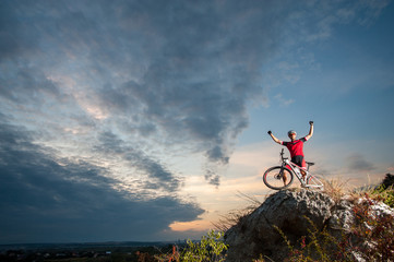 Happy cross country biker celebrates his success on the top of the mountain, enjoying beautiful sunset on overview point.