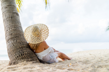 Woman on the tropical beach under the coconut trees