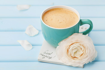 Coffee cup with spring flower and notes good morning on blue rustic background, breakfast on Mothers day or Womens day