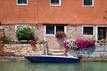 Italian home next to the river with a lot of colorful flowers and a boat near the front door.