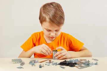 Little boy plays with mechanical constructor at the table