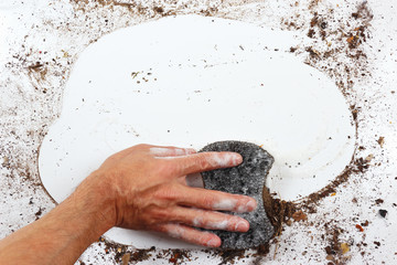 Hand with wet black sponge cleans a very dirty surface