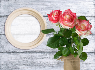 Roses and round photo frame on background of shabby wooden plank
