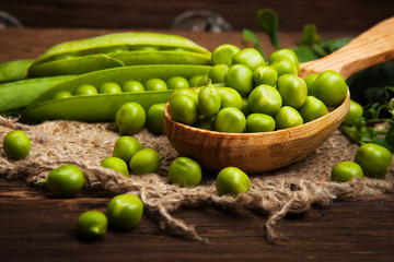 Fresh organic green peas on a wooden background.Rustic style.