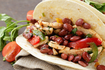 Mexican food is tacos on wheat tortilla with chicken and beans