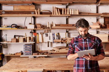 Artisan carpenter in his woodwork studio using digital tablet