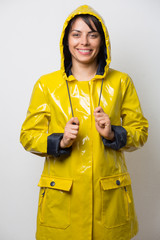 Attractive young woman posing with a yellow raincoat