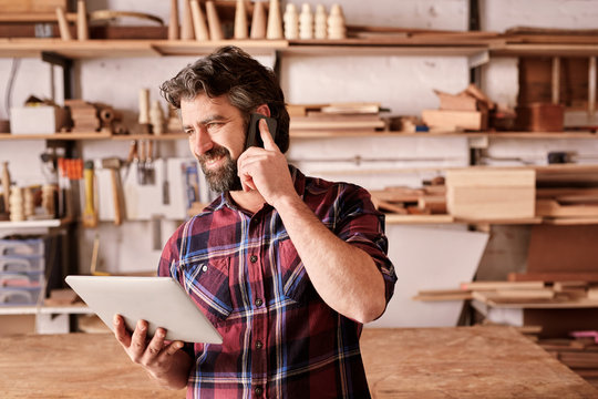Small business owner in workshop with phone and digital tablet