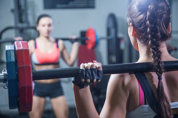 young woman with a barbell in front of the mirror in the gym