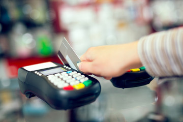 Female hand doing purchase through payment machine