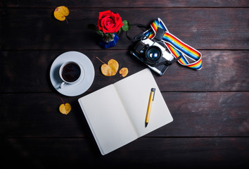 Retro camera, open memo book ,red rose and coffee cup on dard wo