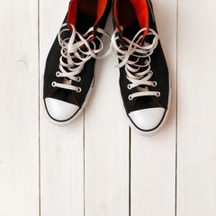 Stylish fashionable black shoes on a white wooden background