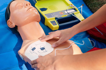Practicing cardiopulmonary resuscitation procedure with CPR dummy and defibrillator,