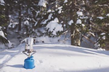 Italian coffee maker on camping gas stove, winter scene