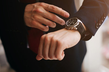 Closeup businessman looks at his watch