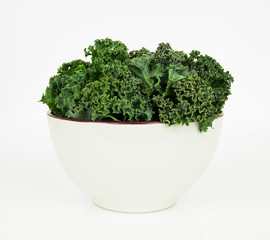 Fresh raw kale in ceramic bowl on the white background