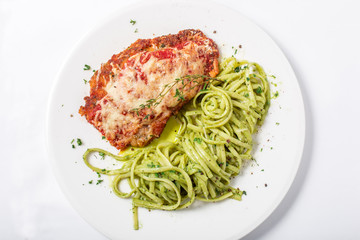 Chicken with parmesan cheese and linguine pasta in pesto sauce