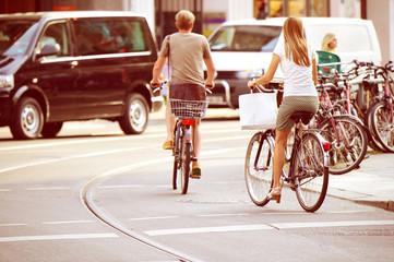Fototapete - People on bikes in traffic