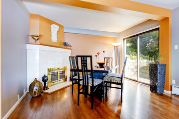 Dinning room with white fire place, hardwood floor, and orange i