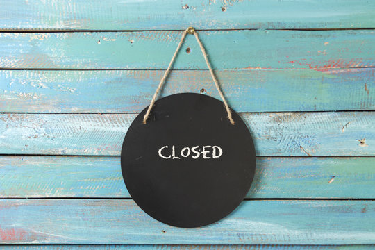 closed sign hanging on blue background
