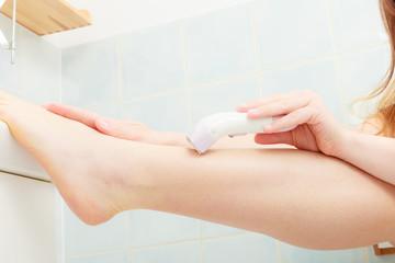 Woman shaving legs with depilator in bathroom