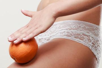 Girl holding orange next to leg