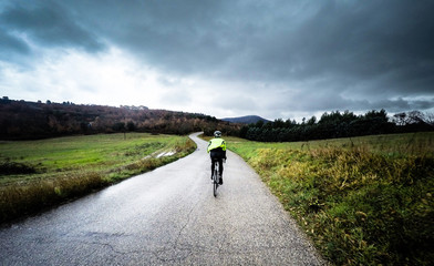 man on a bicycle ride along a mountain road during a storm