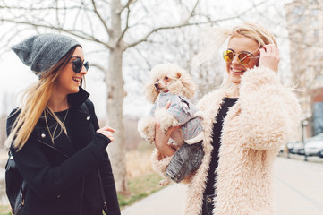 two young caucasian cute girls portrait with dog outdoor in park walking happy and smile all the way